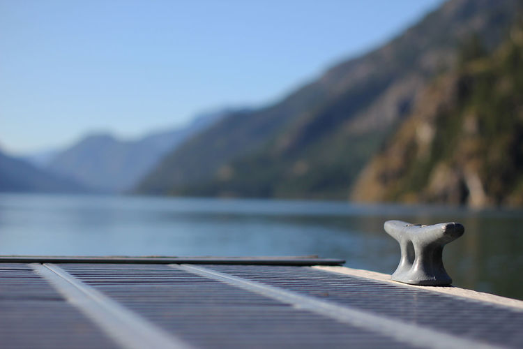 Mooring bollard on pier against lake