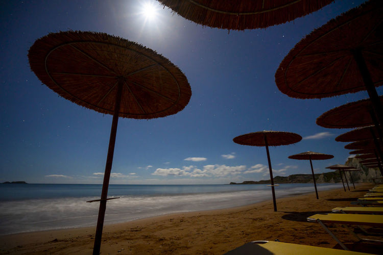 Low angle view of parasols on beach against sky