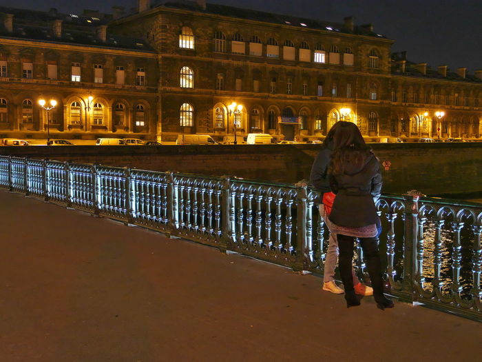 Rear view of woman standing by railing in city at night