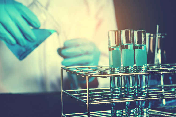 Midsection of scientist pouring chemical in test tube from beaker against black background
