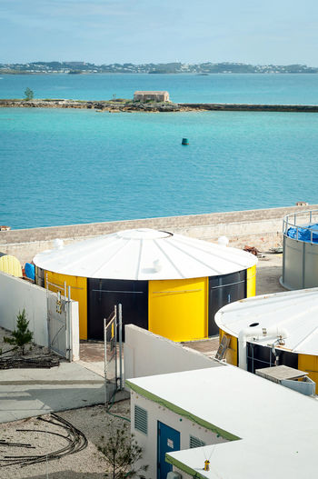 Gas deposits at Bermuda harbor. Architecture Atlantic Beach Beauty In Nature Bermudas Blue Built Structure Container Day Harbor High Angle View Horizon Over Water Island Nature No People Oil Outdoors Scenics Sea Sky Swimming Pool Tranquil Scene Tranquility Water Yellow