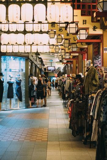 People walking on illuminated store in city