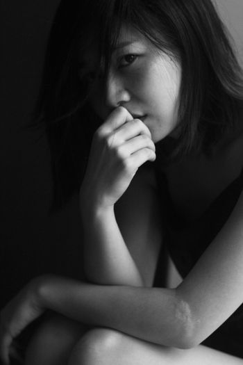 Close-Up Portrait Of Young Woman Depressed Woman Sitting In Darkroom