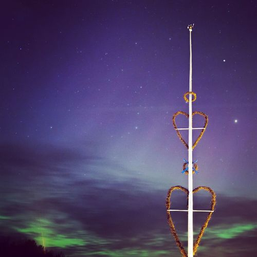Heart shape decorations on pole against aurora in sky at night
