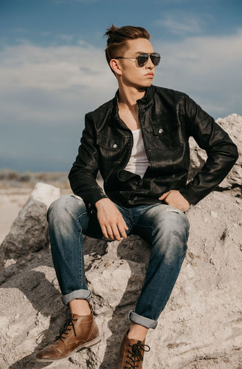 Full Length Of Young Man Sitting On Rock Against Sky
