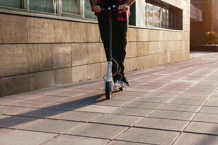 Low section of man riding bicycle on footpath in city