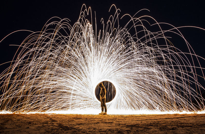 Person with illuminated wire wool on field against sky at night
