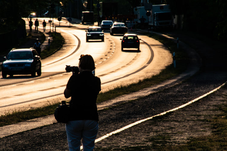 Rear View Of Woman Photographing Street In City At Sunset