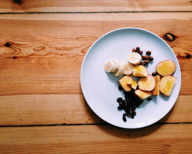 Directly above shot of fruits in plate on wooden table