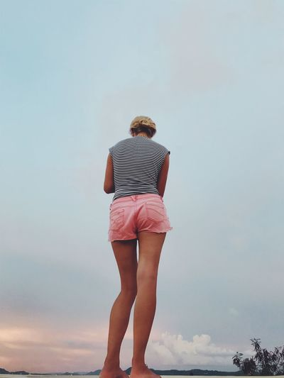 Rear View Of Woman Standing Against Cloudy Sky During Sunset