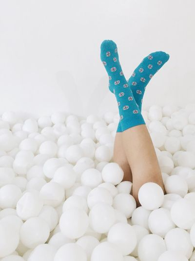 Woman amidst balls against white background