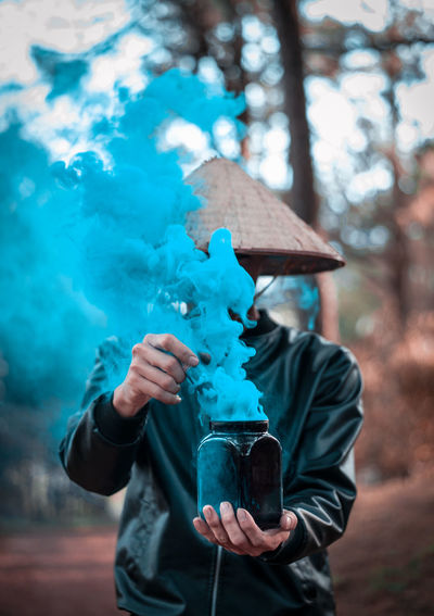 Man holding jar with blue smoke forming by chemical reaction