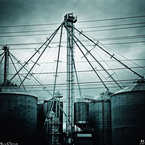 """Industrial Blues. As I was driving my kids to enjoy a Sunday afternoon at a McDonald's Playland I spied this industrial/agricultural set of buildings and decided I had to stop to shoot them. Ellie asked me, """"Why do you always have to stop to take pictur"""