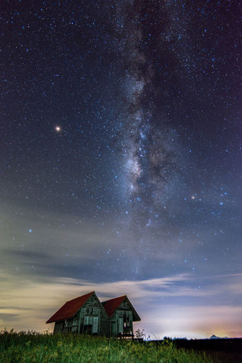 House on field against sky at night