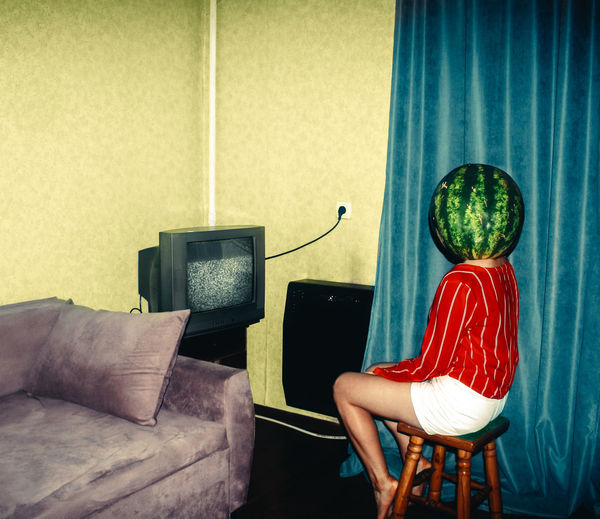 Young woman wearing watermelon on head sitting at home