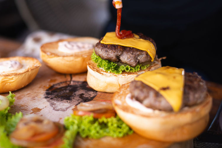 Food Food And Drink Burger Fast Food Ready-to-eat Sandwich Hamburger Unhealthy Eating Indoors  Freshness Close-up Meat Bread Selective Focus No People Bun Lettuce Vegetable Beef Still Life Temptation CheeseBurger Black Background Snack