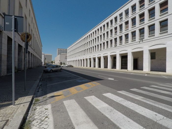 Road by building against sky in city