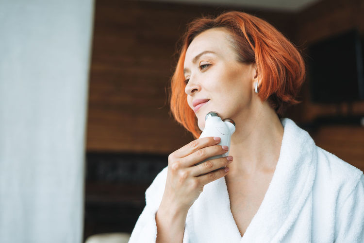 Woman in white bathrobe with red hair doing fasial massage with microcurrent facial massager