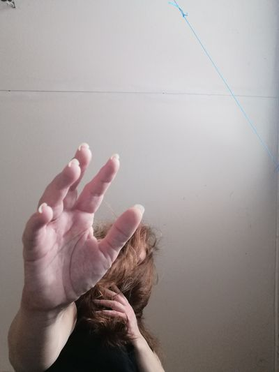 Midsection of woman hand on floor against wall at home