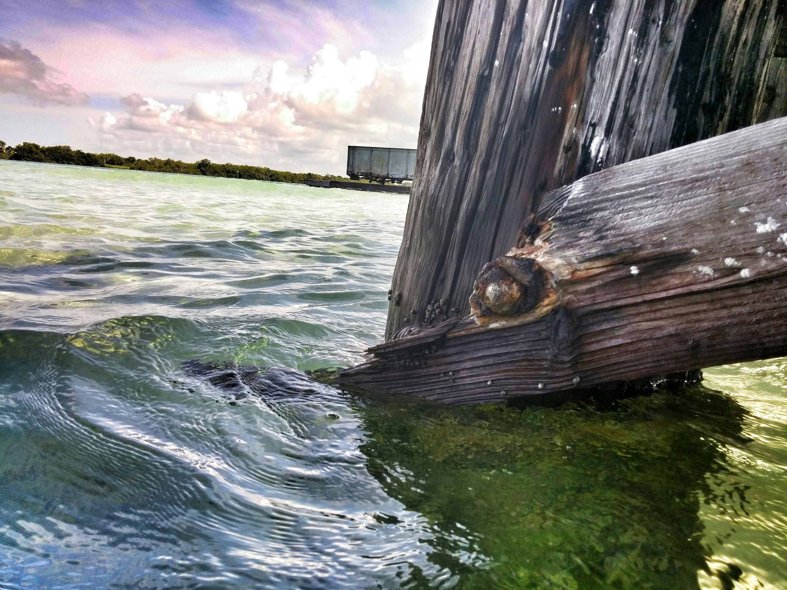 water, sky, sea, cloud - sky, beach, built structure, waterfront, building exterior, cloud, architecture, nature, wood - material, day, outdoors, shore, rippled, beauty in nature, cloudy, tranquility, reflection