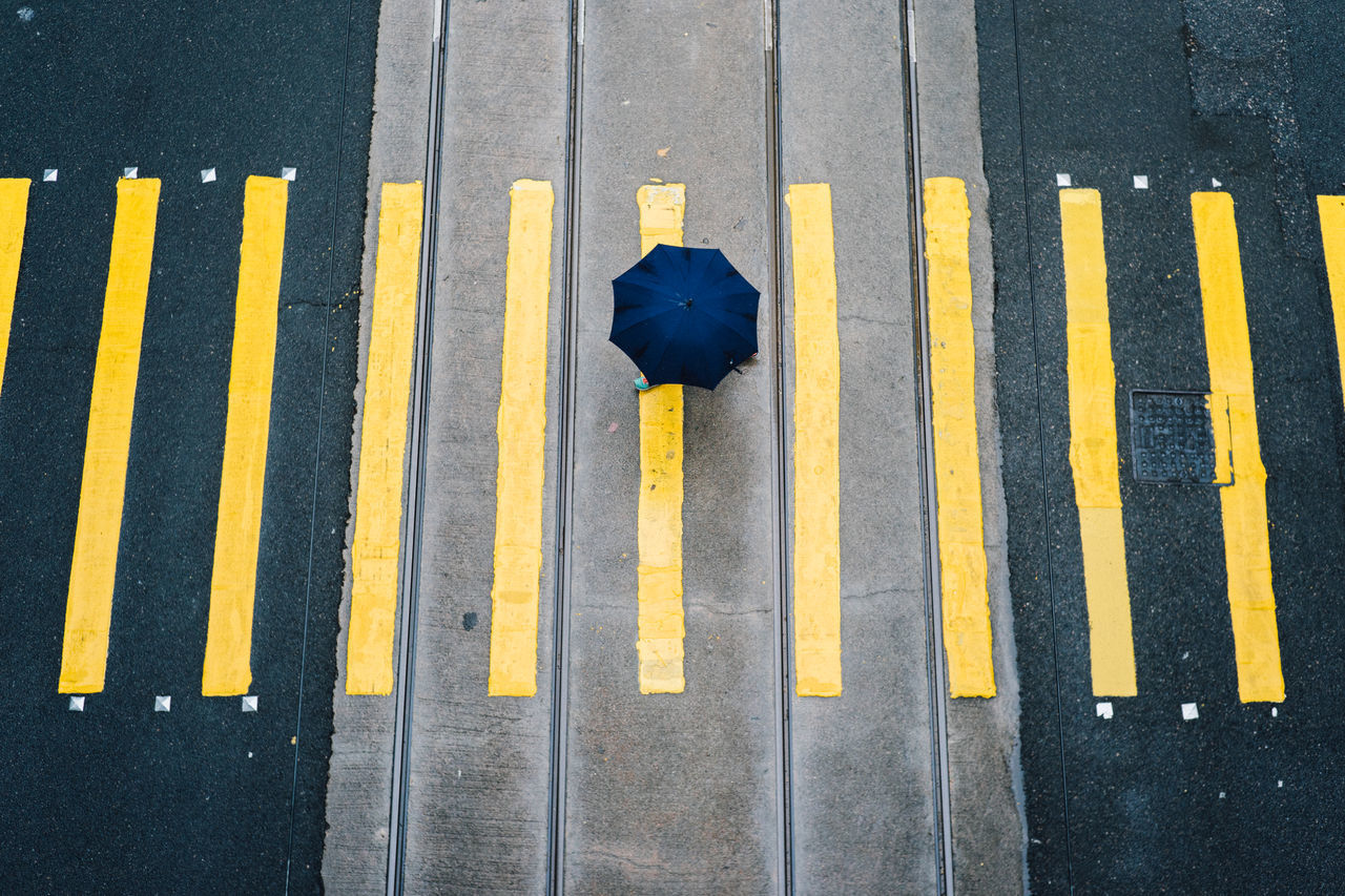 Low section of person with umbrella crossing road