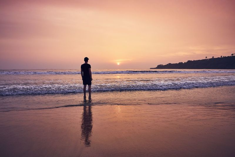 Contemplation during beautiful sunrise. Young man on idyllic sand beach. Man Contemplation Beach Sunrise Sunset Sea Beauty In Nature Scenics - Nature One Person Horizon Over Water Tranquility Pensive Lonely Hope Alone Rear View People Travel Freedom Individuality Reflection Sand Coastline Inspiration Enjoyment