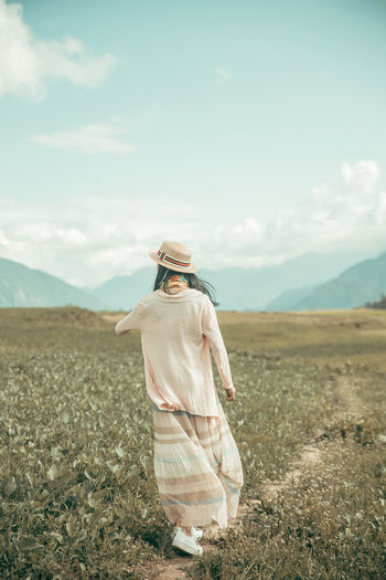 Rear View Of Woman Walking On Footpath Amidst Field Against Sky
