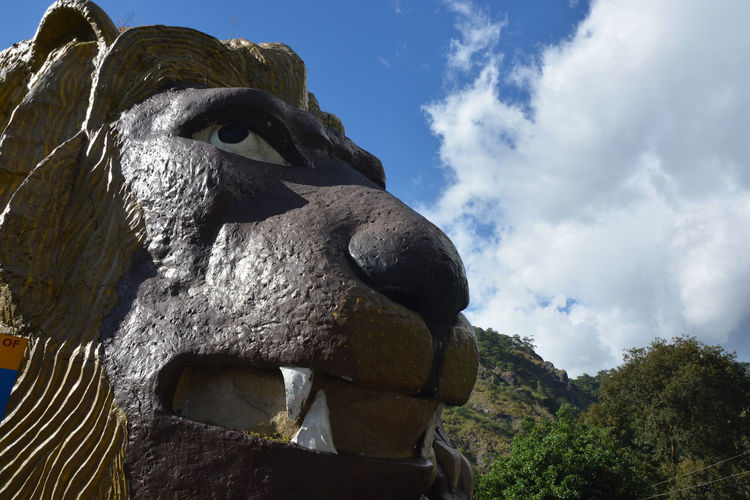 Low angle view of lion statue against sky