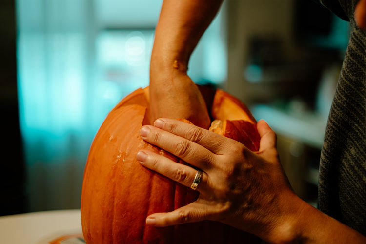 Midsection of person carving pumpkin on table at home