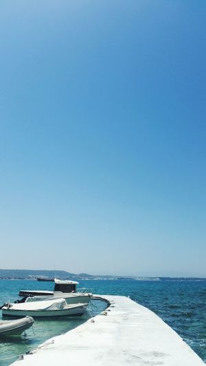 Boats moored in sea by pier against clear blue sky