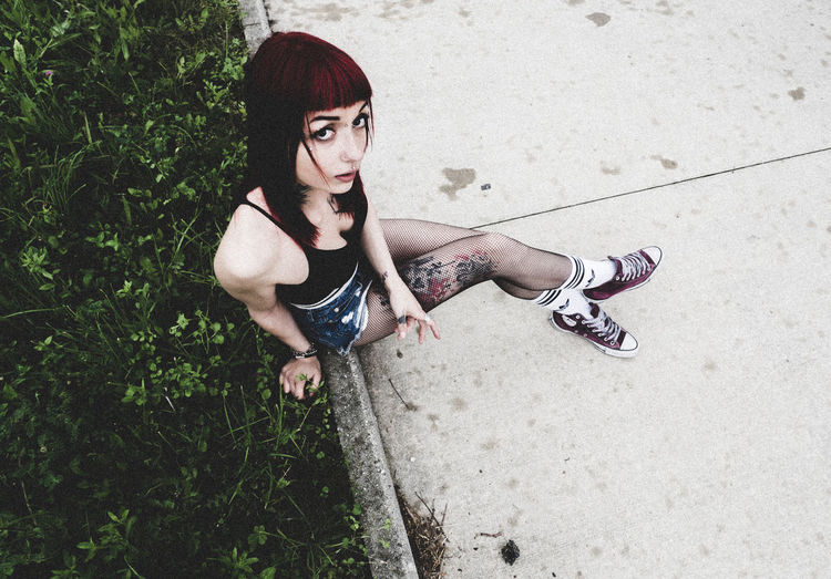 High Angle Portrait Of Young Woman Sitting On Retaining Wall By Plants