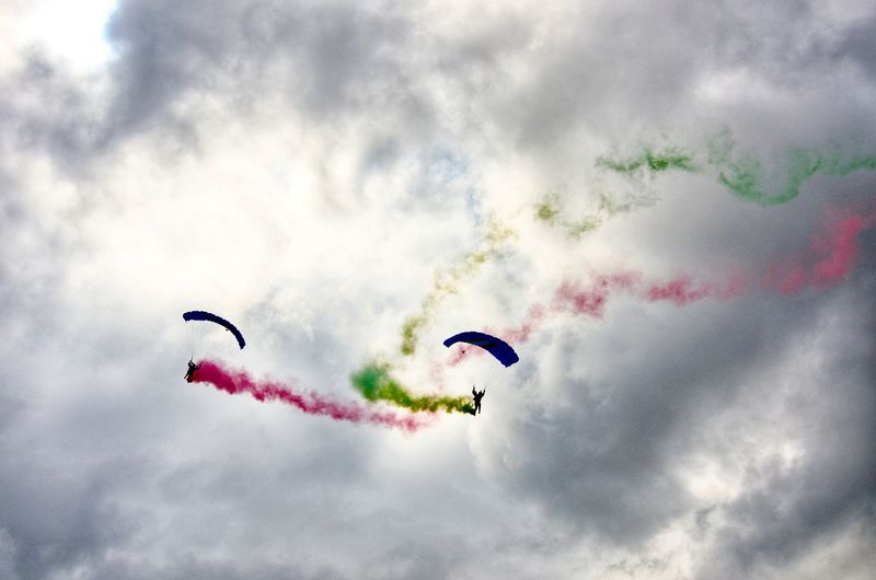 Low angle view of vapor trails and paragliders against cloudy sky