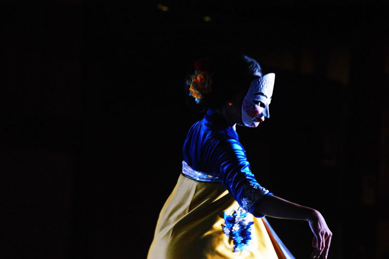 Side view of woman dancing while wearing mask at night