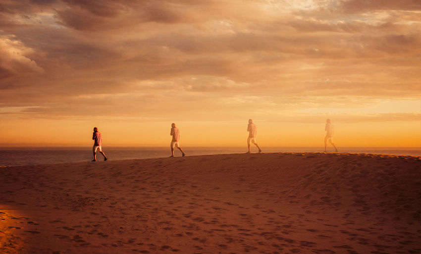 Multi exposure on man walking at beach against cloudy sky during sunset
