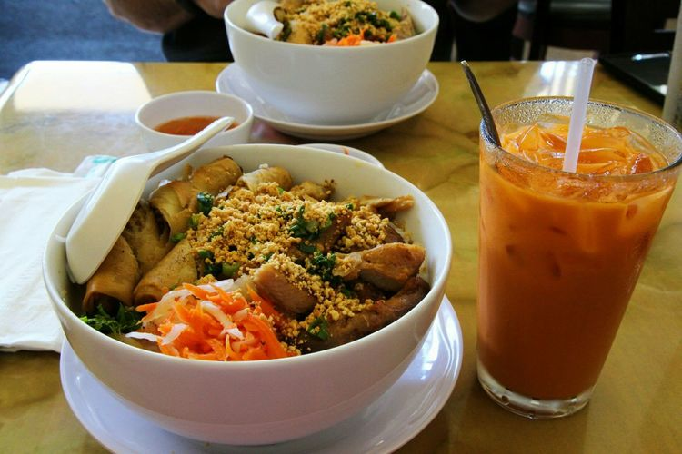Close-up of spring rolls in bowl by drink on table