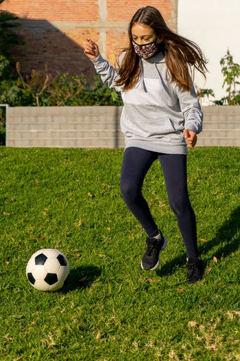 Full length of woman in mask playing with soccer ball at lawn