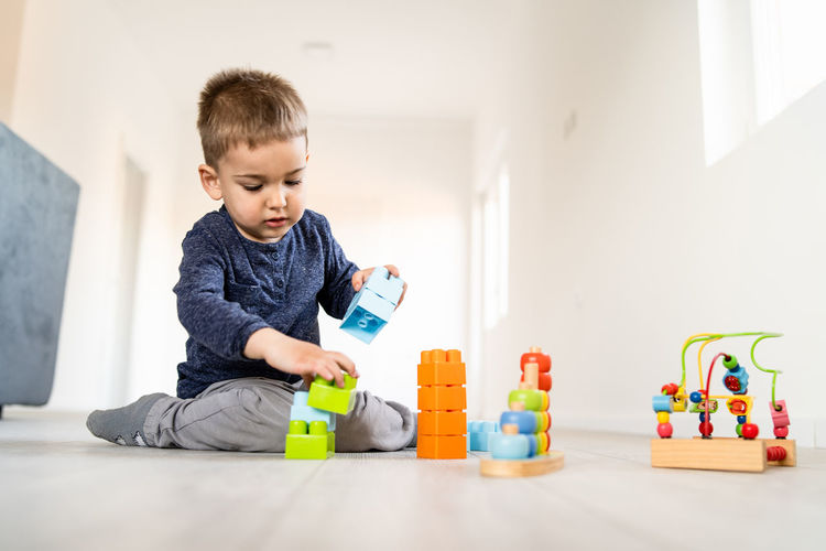Childhood Toy Child One Person Men Real People Indoors  Home Interior Boys Casual Clothing Toy Block Males  Innocence Multi Colored Playing Lifestyles Front View Looking Leisure Activity Flooring