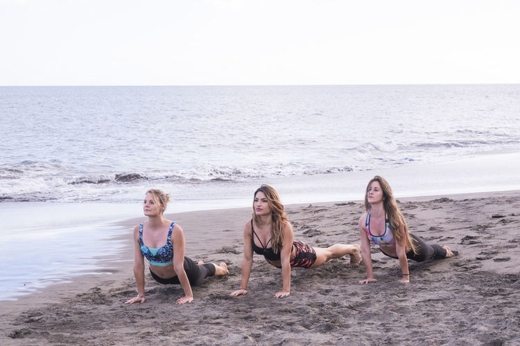 Female friends exercising on shore at beach