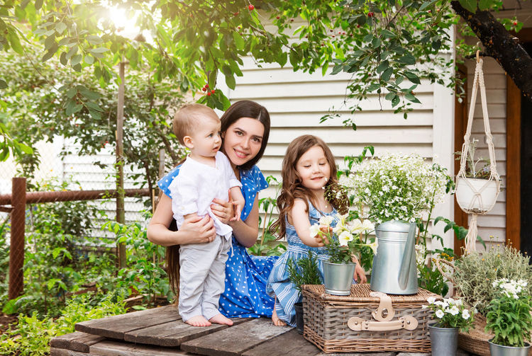 Full length portrait of happy girl standing by basket against plants