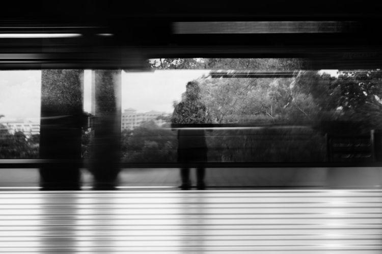 Blurred motion of man walking on train window