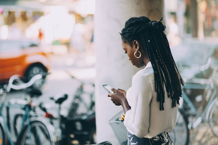 Side view of woman using phone while standing on street