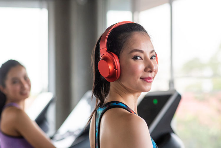 Side view portrait of smiling young woman wearing red headphones while exercising on treadmill in gym