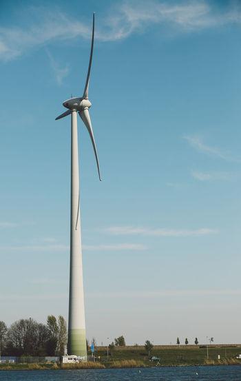 Wind turbine by lake against blue sky