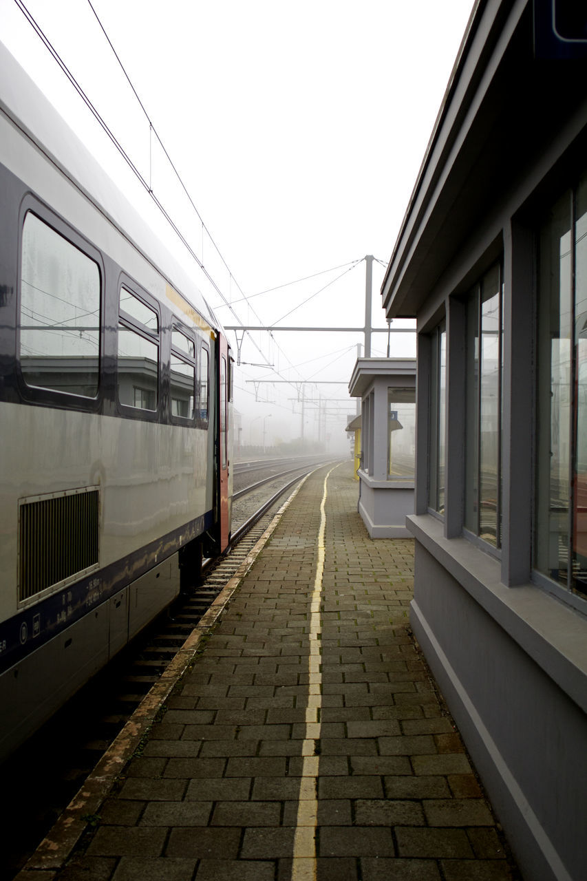 transportation, rail transportation, railroad track, railroad station platform, public transportation, mode of transport, railroad station, train - vehicle, day, outdoors, no people, built structure, fog, sky, architecture