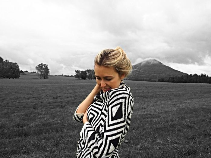 Smiling young woman standing on grassy field against cloudy sky