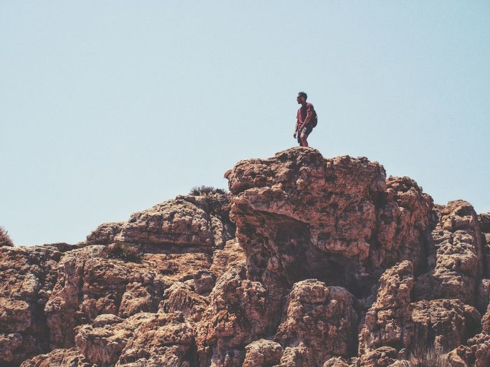 Low angle view of man standing on rock against clear sky