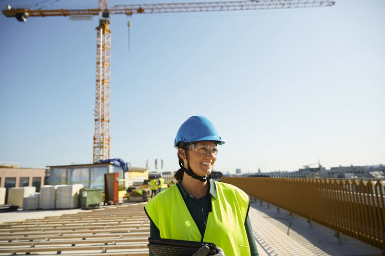 Portrait of smiling man at construction site against sky