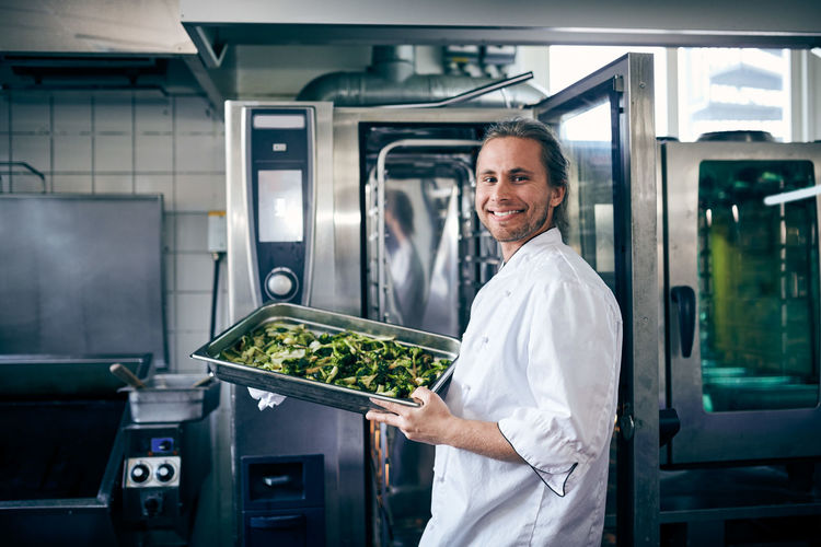 Portrait of smiling man standing in kitchen