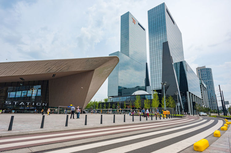 Centraal Station modern building and glass skyscrapers with a crosswalk in the foreground. Crosswalk Road Architecture Building Exterior Built Structure Centraal Station City City Life Day Modern Outdoors Real People Sky Skyscraper Travel Destinations