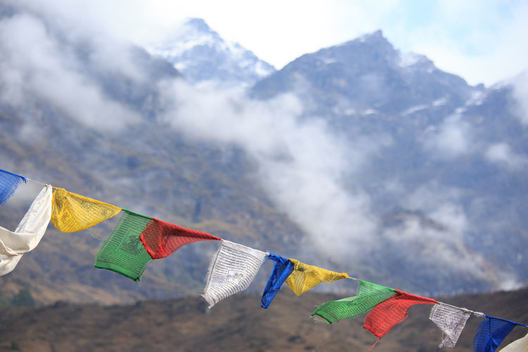 Prayer Flag with snow mountain in the background Himalayas Cloud - Sky Colorful Colors Day Finding New Frontiers Flag India Low Angle View Mount Everest Mountain Mountains Moving Multi Colored No People Outdoors Pray Prayer Prayer Flags  Sikkim Sky Snow Snow Mountain Tibet Wind